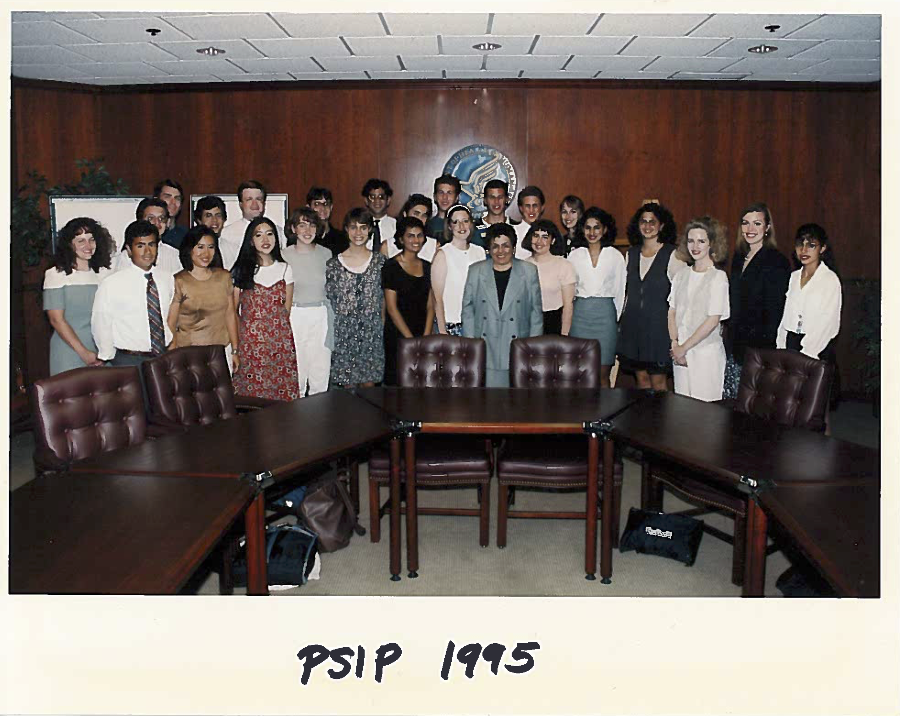 PSIP students standing together behind some chairs and desks