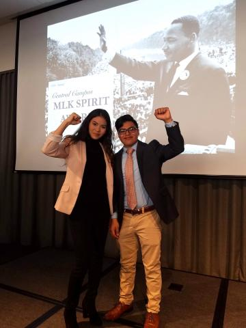 two people, each with one arm raised, with a photo of Dr. Martin Luther King Jr. being projected onto a screen behind them