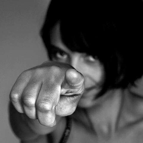 Black and white photo of a woman pointing to the viewer