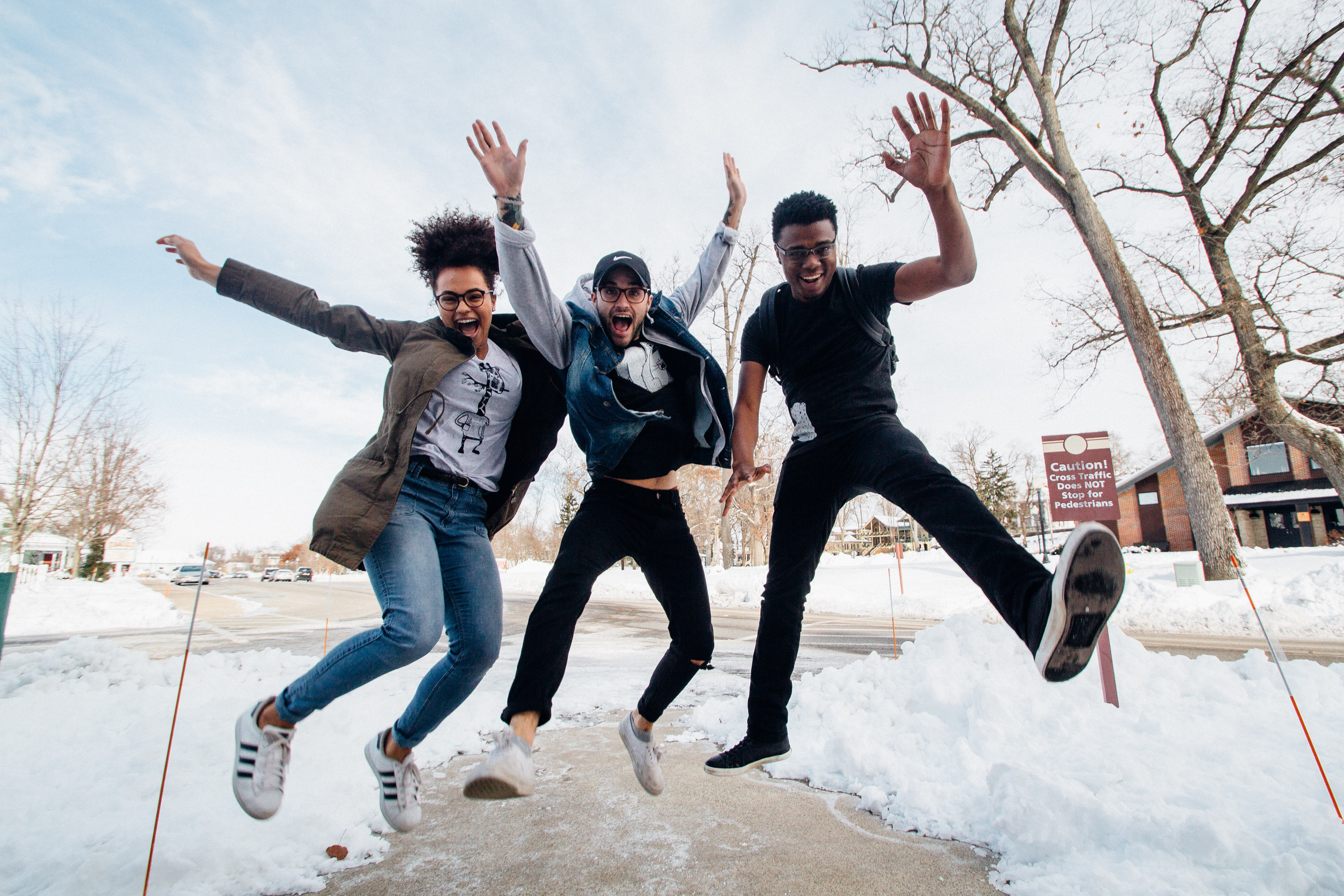 three people jumping in the air, they're on a sidewalk and there is snow on the ground